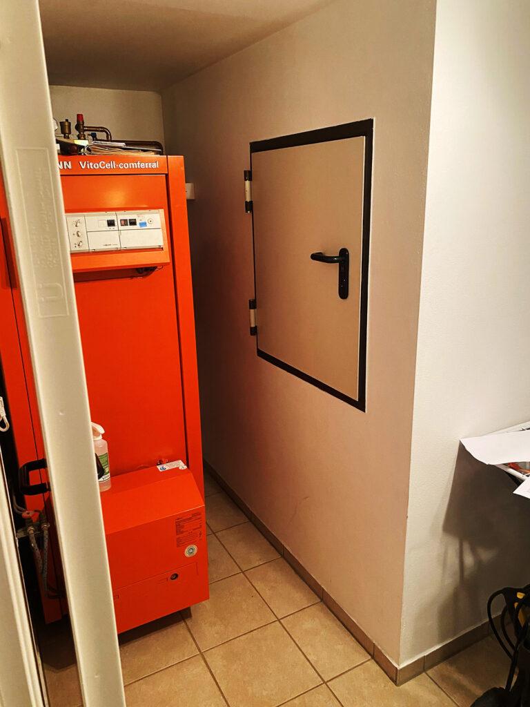 """Eine typische Situation: Der Heizöltank ist hinter einer Tankluke in einem separaten Raum mit Auffangwanne """"versteckt""""."""
