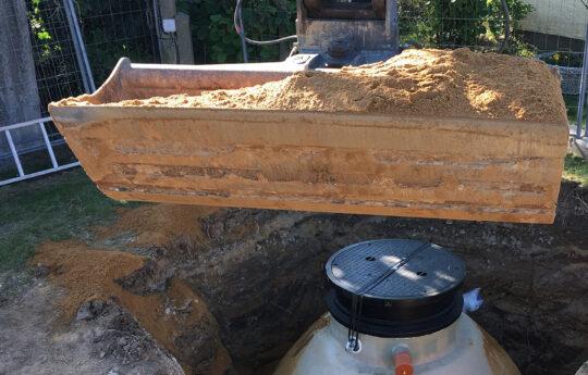 Verfüllen der Baugrube, es kann neben Sand auch Boden oder Kies verwendet werden